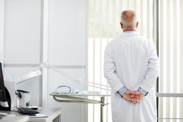 Vista posteriore del dottore senior pensieroso