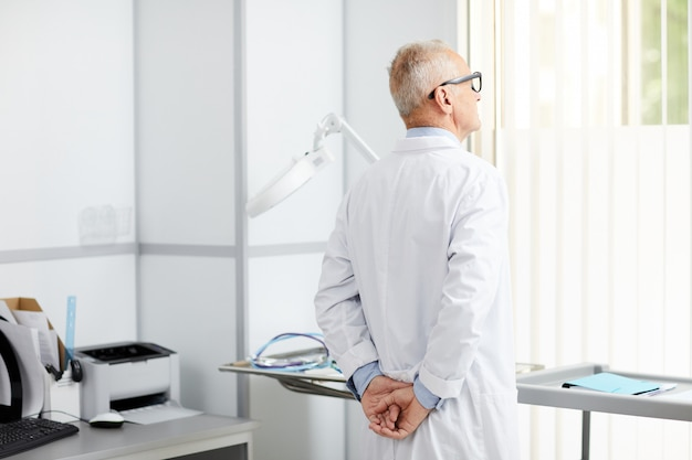 Medico senior pensieroso da window