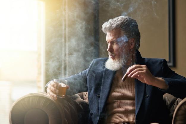 Uomo d'affari maturo ed elegante pensieroso che tiene in mano un sigaro e un bicchiere di whisky mentre si rilassa in un