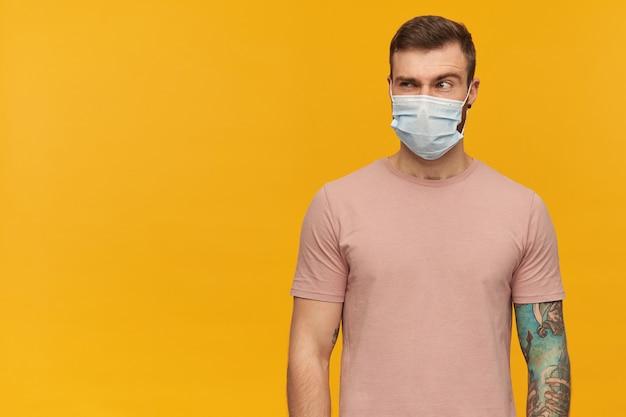 Pensieroso sospettoso giovane uomo barbuto tatuato nella maschera protettiva contro il virus sul viso contro il coronavirus con la fronte sollevata in piedi e guardando lontano oltre il muro giallo