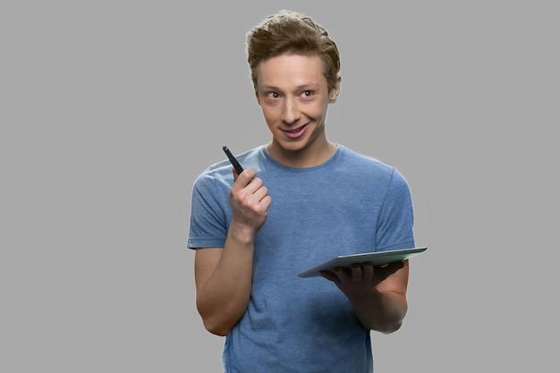 Ragazzo adolescente pensieroso che tiene il tablet pc su sfondo grigio. ragazzo adolescente premuroso che ha un'idea.