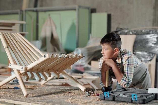 Falegname adolescente pensieroso che si appoggia sul martello mentre guarda la sua sedia di legno finita in officina