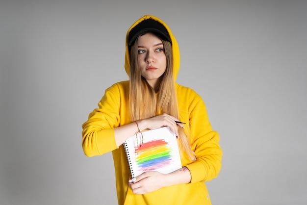 Una donna pensosa con una felpa gialla e un berretto nero tiene in mano un taccuino in cui è disegnato un arcobaleno lgbtq