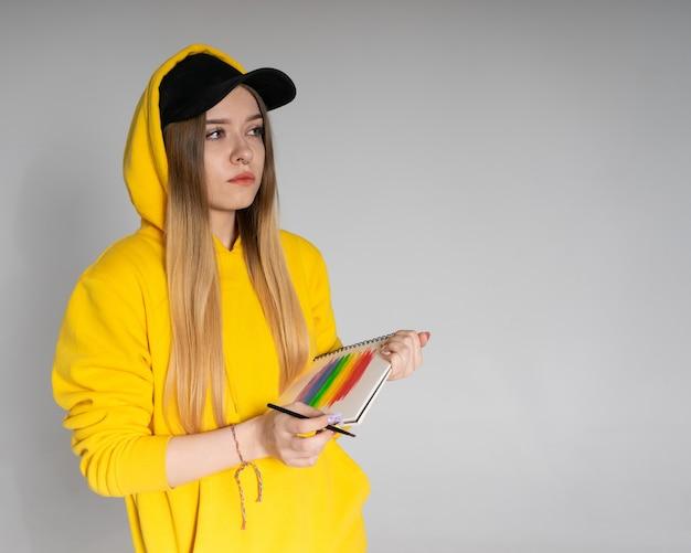 Donna pensierosa in felpa con cappuccio gialla, berretto nero con piercing al naso, che dipinge un arcobaleno lgbtq