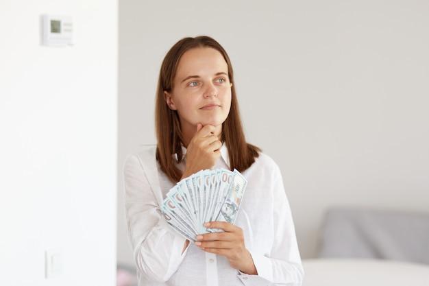 Pensieroso giovane adulto bella ragazza che indossa una camicia bianca in stile casual, con in mano una grossa somma di denaro, tenendo il mento, pensando a un nuovo acquisto, pianificando il suo budget.