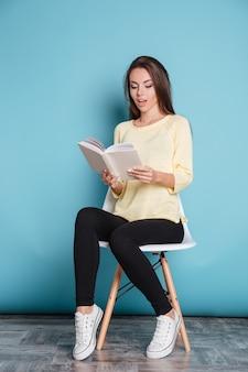 Pensieroso giovane ragazza attraente che legge un libro e si siede su una sedia isolata sullo sfondo blu