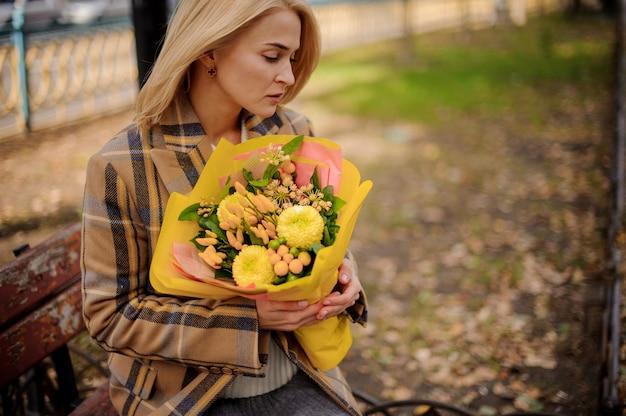 Giovane donna bionda pensierosa in cappotto del plaid che si siede sul banco con un mazzo di fiori gialli