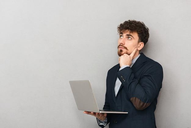 Pensieroso giovane imprenditore che indossa tuta in piedi isolato su grigio, lavorando su un computer portatile