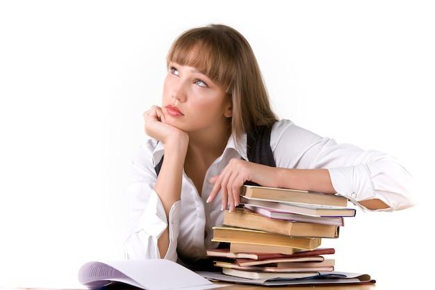 La studentessa pensierosa cerca appoggiandosi sui libri e pensa al futuro. concetto di sogno di professione futura. spazio pubblicitario