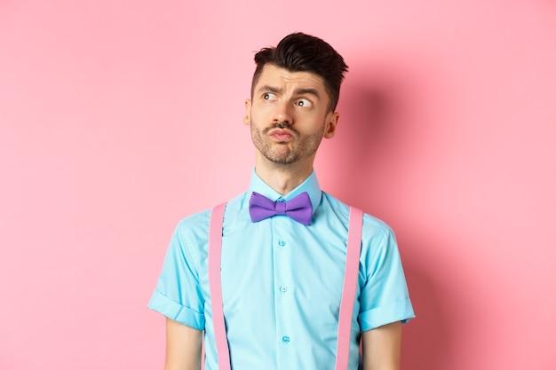 Giovane pensieroso in abito romantico, guardando lontano e pensando, pensieroso in piedi su sfondo rosa in camicia e cravatta fantasia.