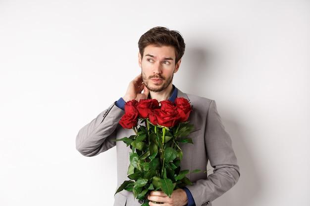Pensieroso giovane uomo in tuta azienda bouquet di fiori, in attesa di data il giorno di san valentino, in piedi su sfondo bianco.
