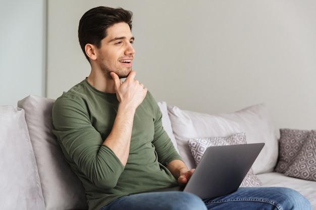 Giovane pensieroso che per mezzo del computer portatile