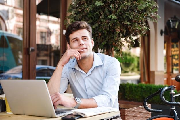 Pensieroso giovane uomo alla moda in camicia che lavora al computer portatile