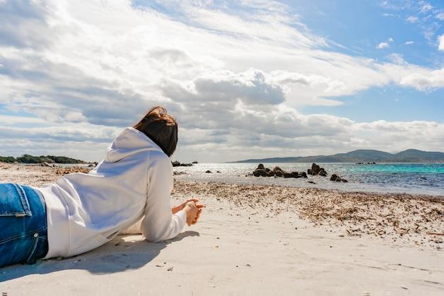 Giovane donna irriconoscibile pensierosa sdraiata sui gomiti sulla sabbia del mare oceano invernale che guarda all'orizzonte e al drammatico cielo nuvoloso sull'acqua in uno scenario surreale. ragazza vestita casual premurosa in jeans