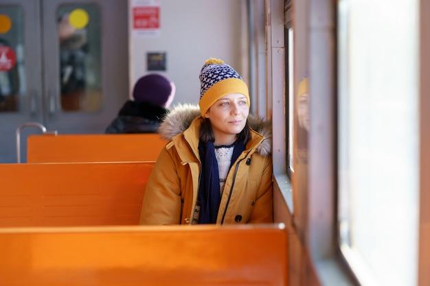 Pensieroso giovane donna che viaggia in treno locale nel periodo invernale, pensando, guardando attraverso la finestra.