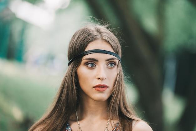 Hippie pensieroso delle giovani donne sullo sfondo del fogliame verde