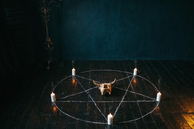 Cerchio del pentagramma con candele sul pavimento di legno nero. rituale di magia oscura con simboli occulti ed esoterici