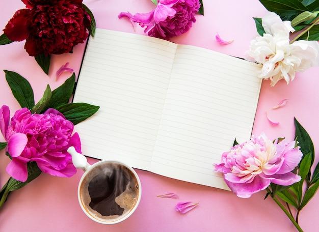 Peonie con blocco note e una tazza di caffè su uno sfondo rosa pastello