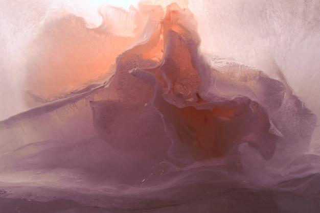Fiore di peonia nel cubo di ghiaccio con bolle d'aria.
