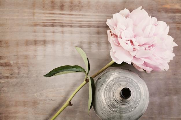 Fiore di peonia su fondo in legno vintage