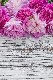Fiori di peonia sulla parete rustica in legno