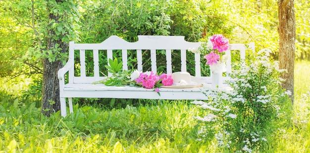 Peonia in brocca su panca in legno bianco nel giardino estivo