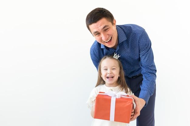 Persone, paternità e concetto di famiglia - papà felice che tiene un contenitore di regalo con sua figlia sul muro bianco con lo spazio della copia