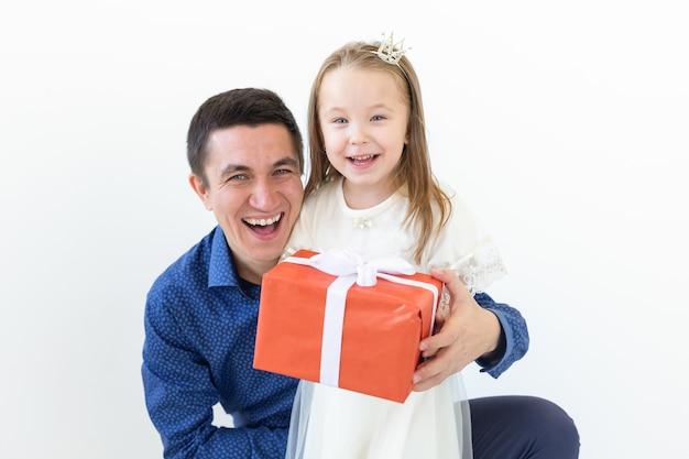 Persone, paternità e concetto di famiglia - papà felice che tiene una confezione regalo con sua figlia su bianco