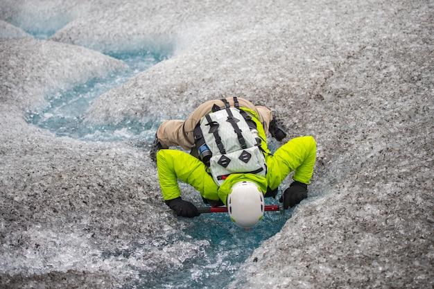 L'azione della gente mostra un'acqua potabile nel ghiacciaio all'islanda, estate