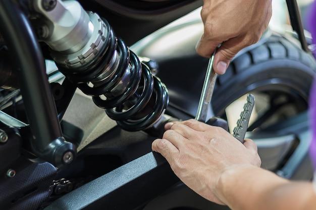 Le persone stanno riparando una moto usa una chiave inglese e un cacciavite per lavorare.