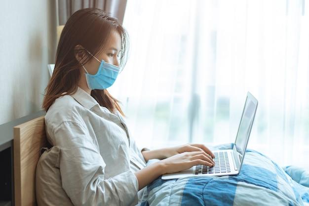 Persone ragazza asiatica adolescente coronavirus influenza infetta che lavora a casa da computer portatile online indossare maschera protettiva per lo smaltimento previene la diffusione del covid-19 in camera da letto.