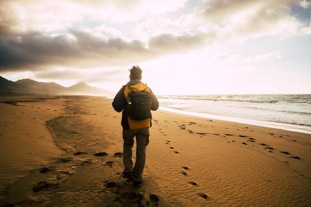 Persone in vista posteriore che camminano da sole con il suo zaino sulla desolazione bellissima spiaggia selvaggia per un concetto alternativo di turismo vacanza avventura ed esplorare la libertà del luogo panoramico e sentire la natura