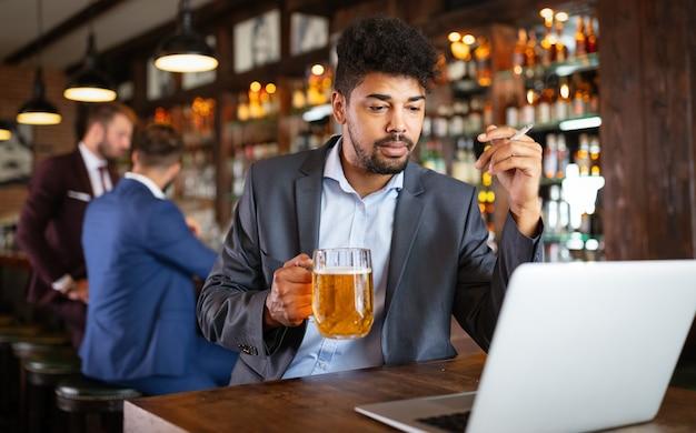 Concetto di persone e cattive abitudini. uomo d'affari che beve birra e fuma sigarette al pub