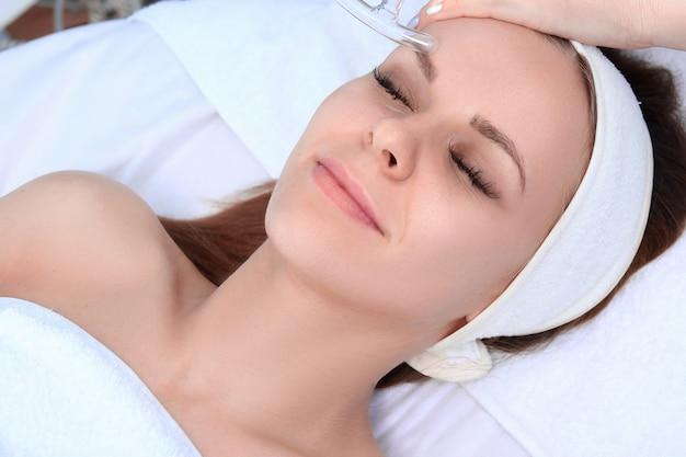 Persone, bellezza, spa, cosmetologia e concetto di tecnologia - primi piani di bella giovane donna sdraiata con gli occhi chiusi con massaggio viso da massaggiatore nella spa.