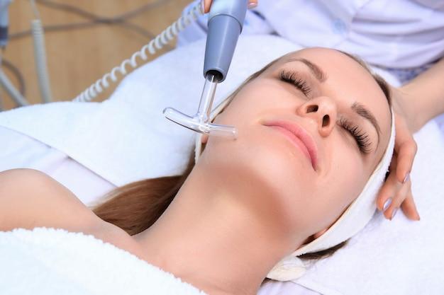 Persone, bellezza, spa, cosmetologia e concetto di tecnologia - primi piani di bella giovane donna sdraiata con gli occhi chiusi con massaggio viso da massaggiatore nella spa. Foto Premium