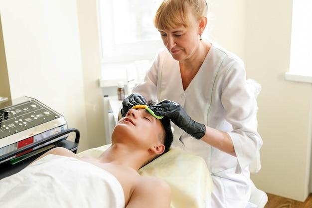 Concetto di persone, bellezza, spa, cosmetologia e tecnologia - il cosmetologo esegue la procedura peeling facciale ad ultrasuoni della pelle del viso di un giovane e bello in un salone di bellezza