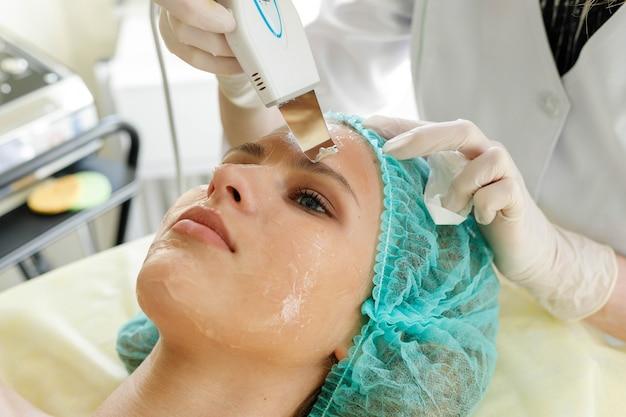 Concetto di persone, bellezza, spa, cosmetologia e tecnologia - il cosmetologo esegue la procedura peeling ultrasonico del viso della pelle del viso di una bella e giovane donna in un salone di bellezza