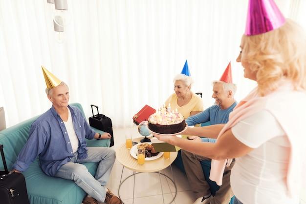 Le persone in un cappello di compleanno gli anziani festeggiano il compleanno