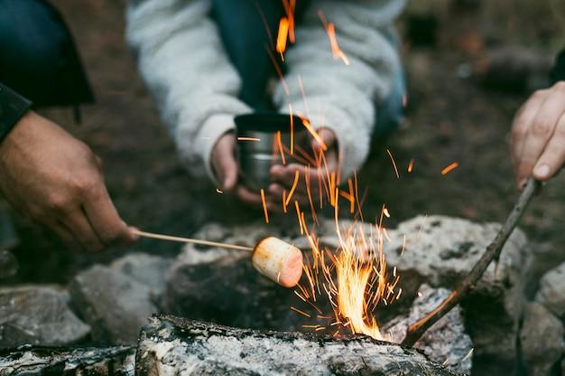 Persone che bruciano marshmallow nel fuoco da campo