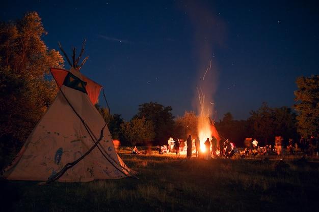 Persone in campeggio in una foresta di notte