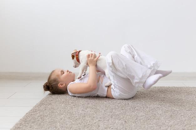 Concetto di persone, bambini e animali domestici - bambina sdraiata sul pavimento con un simpatico cucciolo jack russell terrier