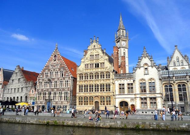 La gente rilassarsi presso il fiume lungo il vecchio porto di graslei nel pomeriggio soleggiato, gand, belgio