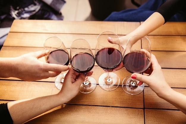 Persone che tintinnano bicchieri di vino sulla terrazza estiva del bar o del ristorante. amici allegri felici celebrano la festa estiva o autunnale. immagine ravvicinata di mani umane, stile di vita.