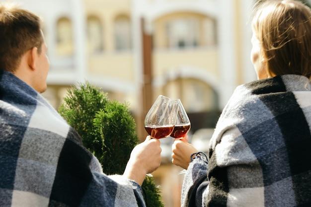 Persone che tintinnano bicchieri di vino sulla terrazza estiva del bar o del ristorante.