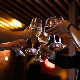 Persone tintinnano di bicchieri di vino al ristorante