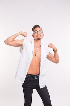 Concetto di persone, abbigliamento e stile - giovane uomo bello in posa in camicia bianca.