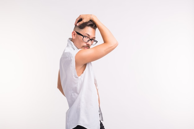 Concetto di persone, abbigliamento e stile - giovane uomo bello sexy che posa in camicia bianca su superficie bianca con lo spazio della copia