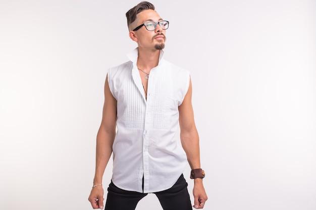 Concetto di persone, abbigliamento e stile - giovane uomo bello sexy che posa in camicia bianca su superficie bianca
