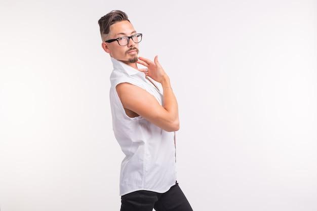 Concetto di persone, abbigliamento e stile - giovane uomo bello sexy che posa in camicia bianca con lo spazio della copia