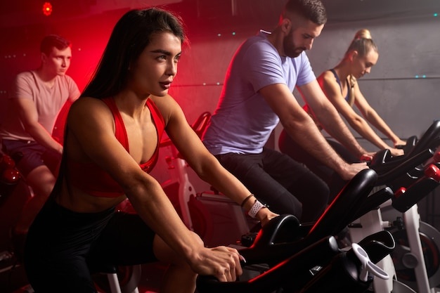 Le persone si sono concentrate sull'assunzione di perdita di peso con la macchina aerobica per il corpo snello, seduti sulla bicicletta, allenamento cardio intensivo in palestra